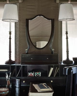 Close-up of a dark-wood shield-shaped mirror with two tall lamps either side