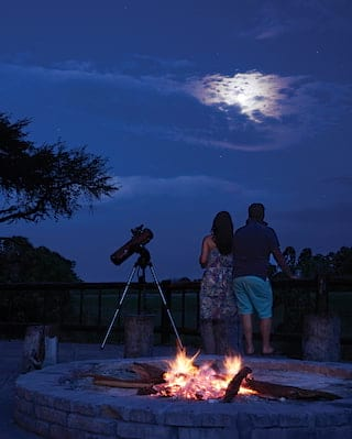 Couple with a telescope next to a campfire looking up at the night sky