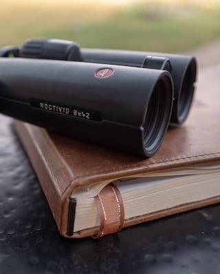 Leica binoculars set atop a journal