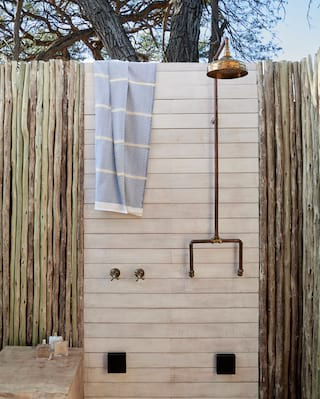 Outdoor brass effect rain shower, shielded by a wooden baton screen
