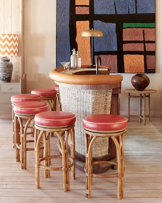 Circular red-leather bar stools around a contemporary rattan bar counter