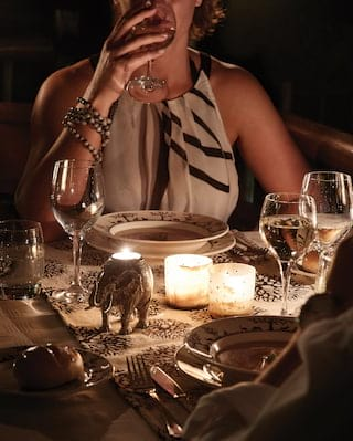 Lady in a zebra print dress at a candlelit table sipping from a wine glass