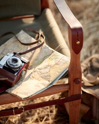Old-fashioned camera with leather strap on top of a map and deck chair