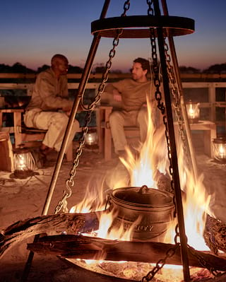 Iron pot in a roaring fire pit surrounded by guests at sundown