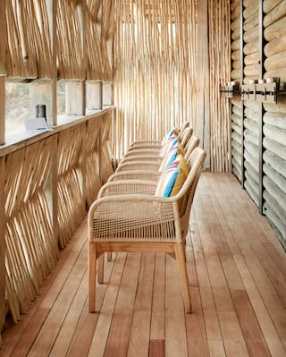 Comfy rattan chairs facing a viewing window in a luxurious wooden game hideout