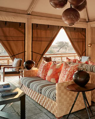 Safari lodge lounge with canvas curtains and African-style decorative pieces