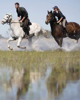 A couple on horseback splashing through flooded grasslands
