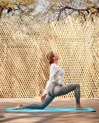 Lady in a warrior yoga pose on a turquoise mat in front of a rattan screen
