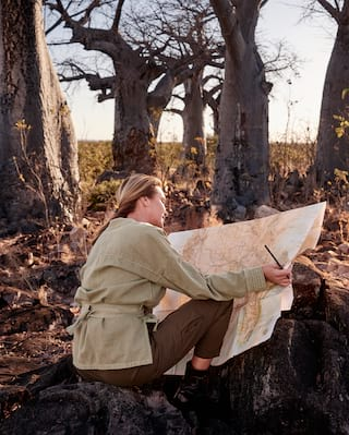 Lady in a khaki outfit kneeling down and studying a map among bushland