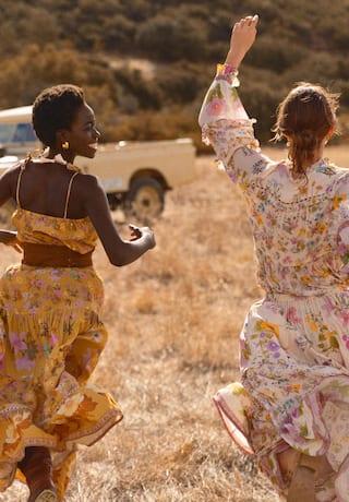 Due donne corrono felici nelle praterie della savana