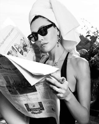 Black and white photo of a lady in a swimsuit reading a newspaper