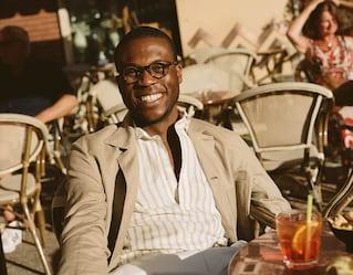 Homem sorrindo vestindo uma camisa listrada sentado à uma mesa ao ar livre