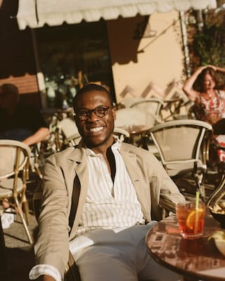 Smiling man drinking a cocktail at an outdoor restaurant table