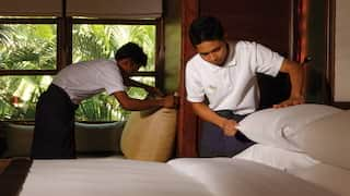 Two housekeepers making a bed in a hotel room with views of palms