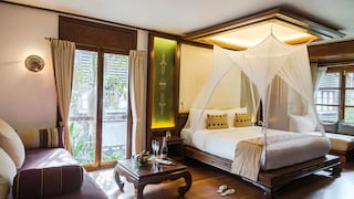 Light and airy hotel room in a Burmese-colonial style with polished hardwood floors
