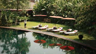 Row of sunbeds and manicured lawn lining an calm outdoor pool