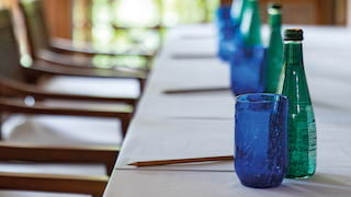 Close-up of blue glasses and green glass water bottles on a banquet table