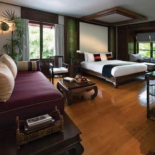 Hotel room with polished hardwood floor and green accents in colonial Burmese style