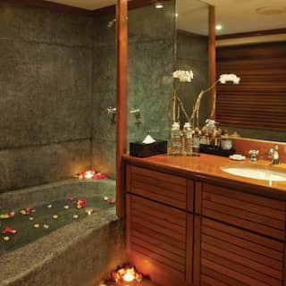 Hotel room bathroom with filled candlelit bath and floating petals