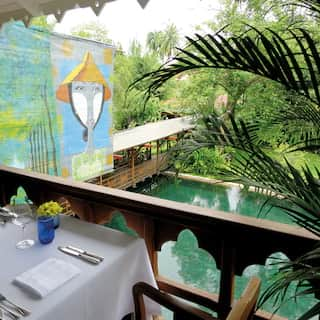 Restaurant table on an open terrace overlooking artwork in a Burmese garden