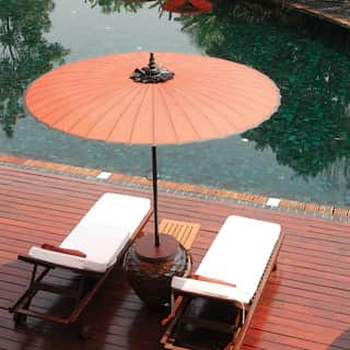 Two sunbeds under an orange parasol on a wooden decking above a glittering pool