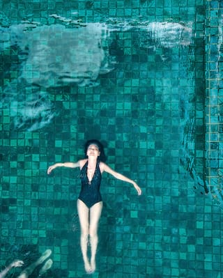 Lady floating blissfully in an outdoor pool