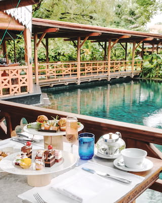 Outdoor table laden with afternoon tea dishes next to an emerald tiled outdoor pool