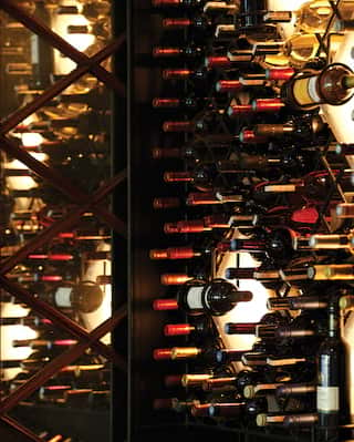 Close-up of a back-lit wall wine rack filled with bottles of red wine