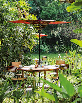 Lone table with a red parasol nestled among lush Burmese gardens