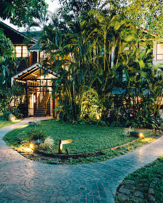 Stone path winding between colonial villas surrounded by bamboo plants and tall palms