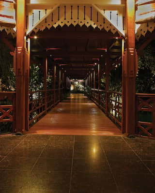 Circular teakwood veranda with at night with a walkway leading away
