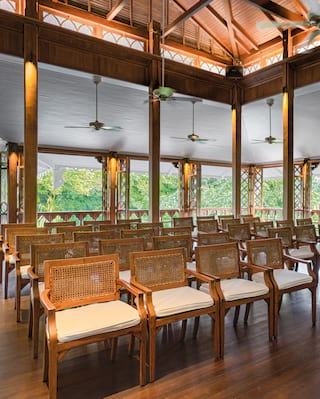 Rows of wooden chairs in an open air venue with a high ceiling