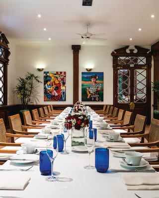 Long banquet table on a light room surrounded by modern artwork