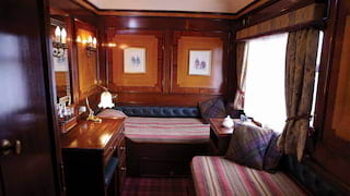 Two single beds in an 'L' formation in an Edwardian-style train cabin