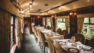 Tables-for-four lining a wood-panelled dining car with elegant window drapes