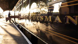 Sun reflected in a burgundy train carriage with 'Scotsman' in gold lettering