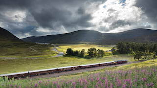 Burgundy train carriages sweeping through a green valley under dramatic rain clouds