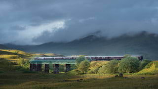 Burgundy train carriages crossing a steel bridge under dramatic misty skies