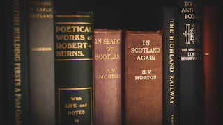 Close-up of old, faded library books, including works by Robert Burns