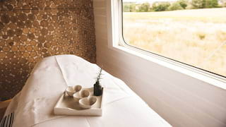 Essential oils in heart-shaped bowls on a massage table in a barn-style spa cabin