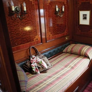 Single bed in a gleaming French-polished wood-panelled train cabin