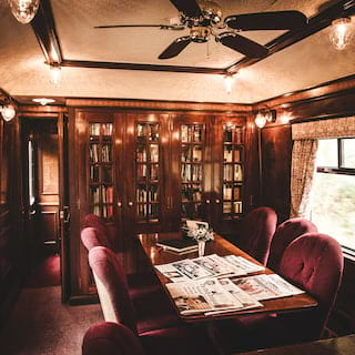 Wood-panelled train dining car with red velvet chairs and banquet tables