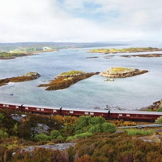 Burgundy train carriages curving alongside a rugged loch dotted with little islands