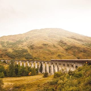 An arched stone rail viaduct curving across a mountainous valley