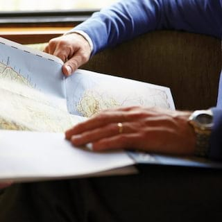 Close-up of hands holding open a paper map of Scotland