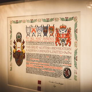A coat of arms certificate in medieval lettering in a glass frame