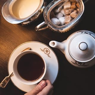 Birds-eye-view of coffee in a gold-rimmed teacup next to a matching teapot