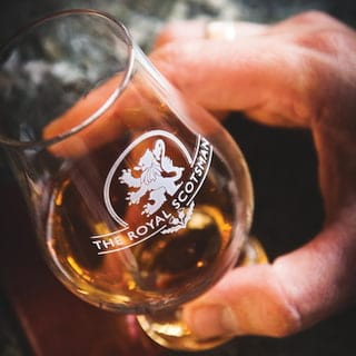 Close-up of whisky in a Glencairn glass engraved with the Royal Scotsman logo