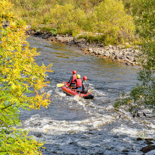 Three people in red life jackets in a river raft sailing past white water rapids