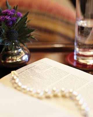 Close-up of a pearl necklace draped across an open book on a mahogany desk